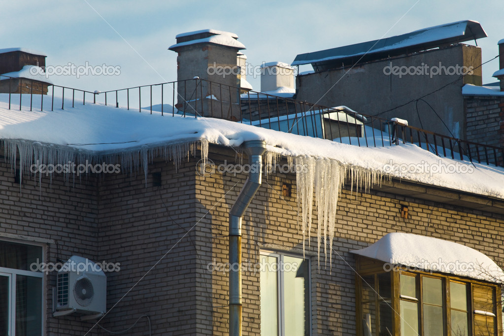 Huge icicles hang down from roof, presenting danger for the persons down. — Stock Photo #2195762
