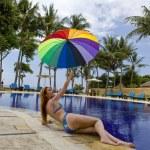 Woman at pool under a colour umbrella — Stock Photo #2229305