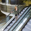 Young woman on the escalator — Stock Photo