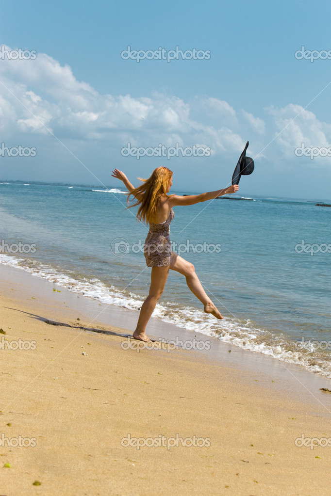 Young graceful woman goes on coast of ocean with straw hat in hands  Stock Photo #2383583