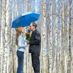 Man gives girl bouquet under umbrella — Stock Photo #2489392