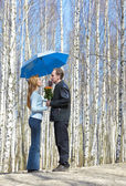 Man gives girl bouquet under umbrella — Stock Photo
