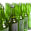 Stock Photo: Empty glass bottles and one full