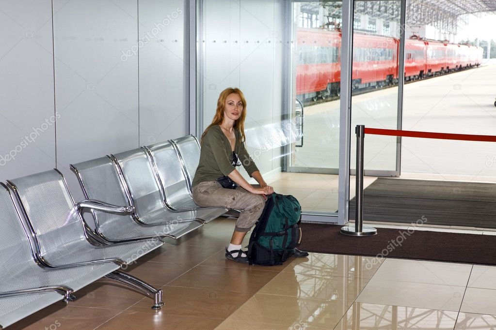 The girl with a road backpack in a station waiting room — Stock Photo #2533287