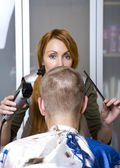Pretty woman hairdresser cuts client — Stockfoto