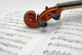 Violin scroll resting on a sheet music — Stock Photo