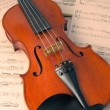 Violin resting on music scores — Stock Photo