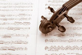 Vintage violin neck over sheet music — Stock Photo