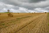 Gammal väderkvarn i ett fält med halm balar — Stockfoto