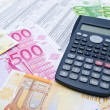Euro banknotes and calculator - Stock Photo
