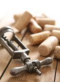 Corkscrew and some corks — Stock Photo