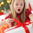 Teenage girl opening her christmas pre - Stock Photo