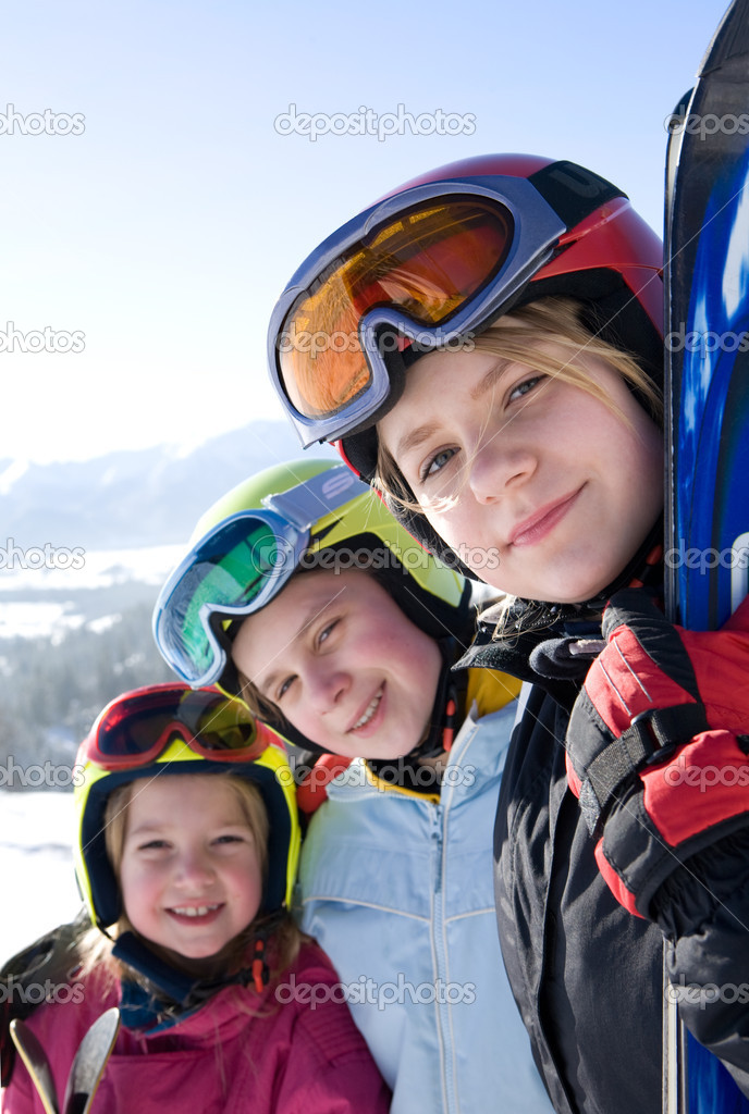 Young smiling girls wearing ski goggles. Mountains in background.  Stock Photo #1964903