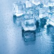 Ice cubes in blue ambient light. — Stock Photo