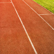 Green grass and running track - Stock Photo