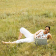 Woman on the grass with laptop — Stock Photo