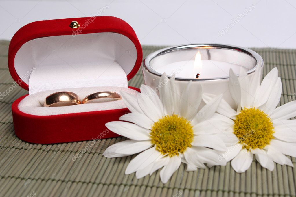 Small box with weddings rings next to  candle and camomiles!  Stock Photo #1995361