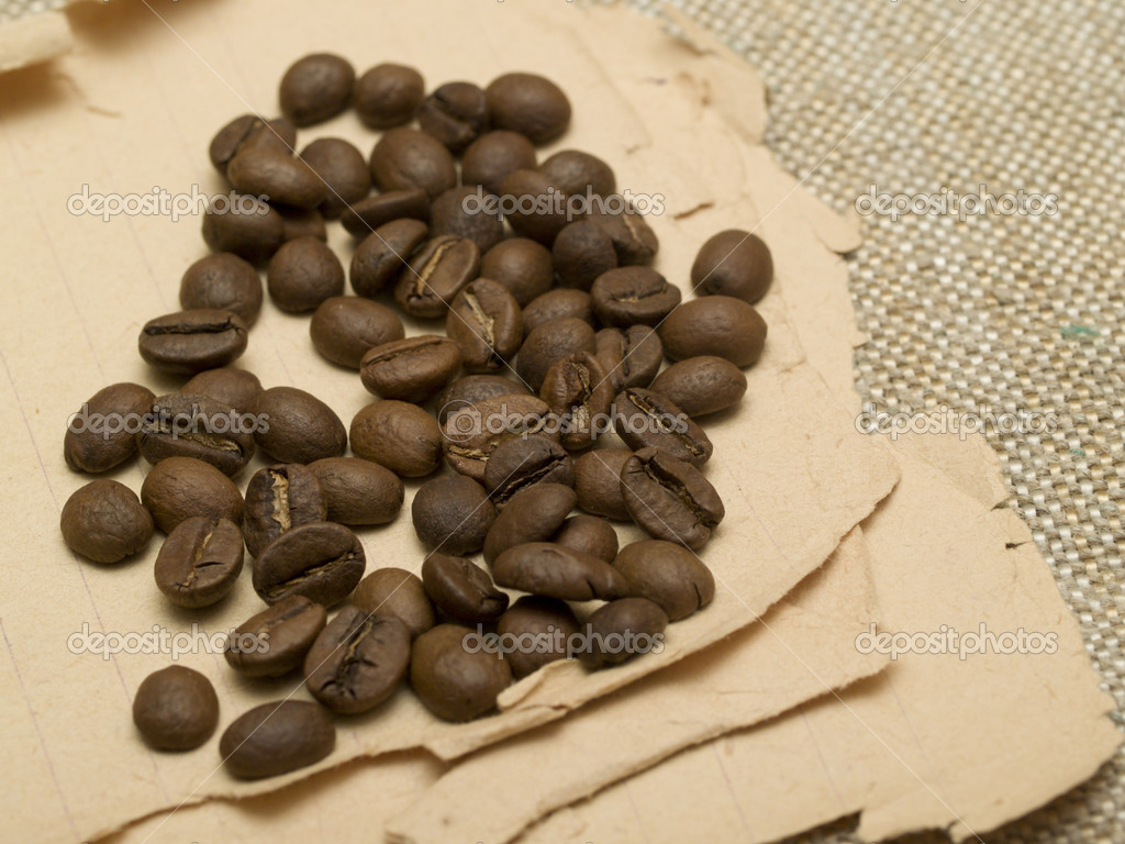 Coffee beans scattered on the old paper — Stock Photo #1830187