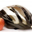 Bicycle helmet and apple - Stock Photo