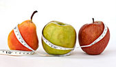 A pear and apples with measuring tape — Stock Photo