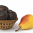 Pear and basket of plums — Stock Photo