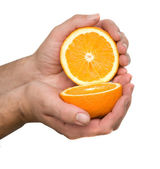 Hand holding halves of orange — Stock Photo