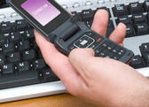 Cellular phone and computer keyboard — Stock Photo