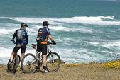 Two cyclists on sea beach — Stock Photo