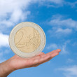 Two euro coin in hand on sky background backgrou — Stock Photo