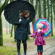 Mother with daughter under umbrellas — Stockfoto