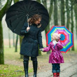 Mother with daughter under umbrellas — Stock Photo