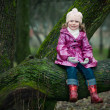 Girl sits on a tree — Stock Photo