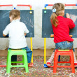 Girl and boy drawing on the blackboard — Stock fotografie