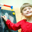 Stock Photo: Girl draws with chalk on the blackboard