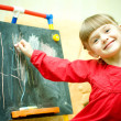 Girl draws with chalk on the blackboard — Stock Photo