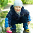 Little boy plays with ship in puddle — Stock Photo #1951323
