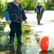 Boy with ball in puddle — Stock Photo #1951325