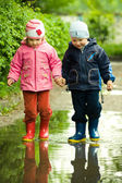 Boy and girl in the puddle — Stock Photo