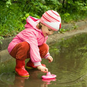 Girl playing with ship in the puddle — Stock Photo
