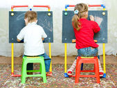 Girl and boy drawing on the blackboard — Stock Photo