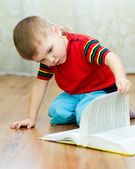 A little boy reads a book — Stockfoto