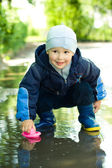 Little boy plays with ship in the puddle — Stock Photo