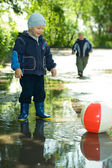 Boy with ball in the puddle — Stock Photo