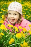 Funny girl in dandelions — Stock Photo