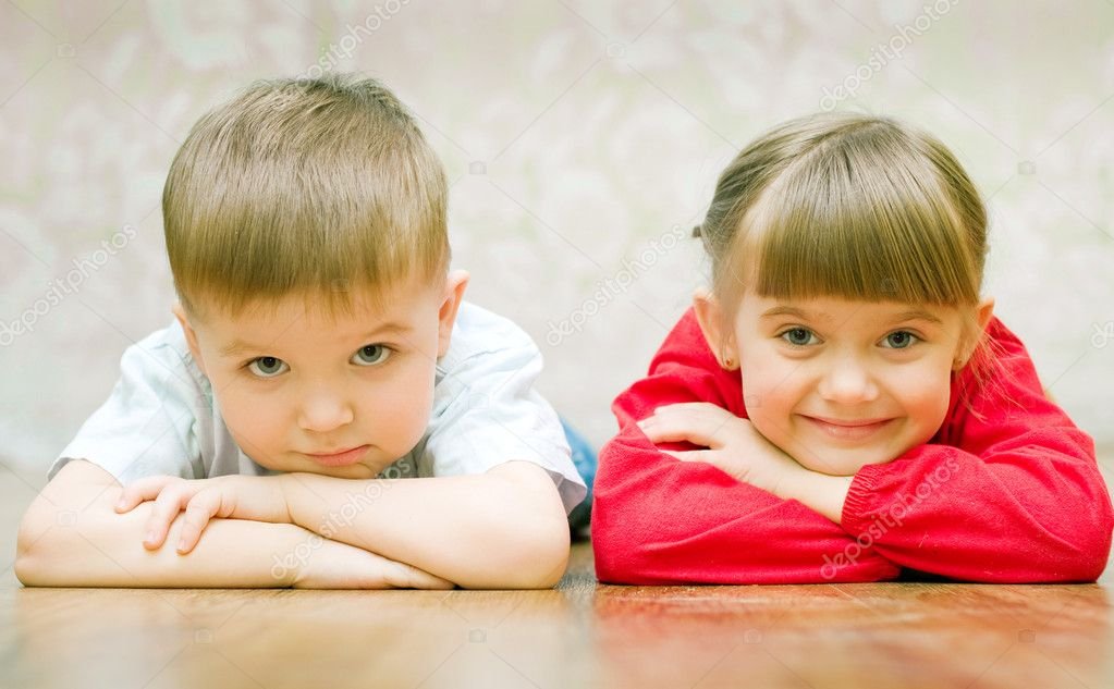 Funny boy and a girl lying on the floor — Стоковая фотография #1951168