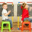 Girl and boy drawing on the blackboard - Stock Photo