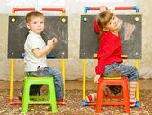 Girl and boy drawing on the blackboard — Stock Photo