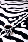 Zebra cup on zebra carpet — Stock Photo
