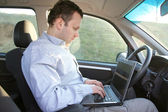 Laptop behind steering wheel — Stock Photo