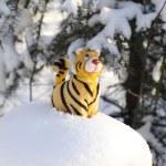 Statuette tiger on snow-bound stub — Stock Photo #1854098
